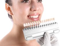 Dentysta sprawdza młoda kobieta zęby barwi na białym tle fotografia stock
