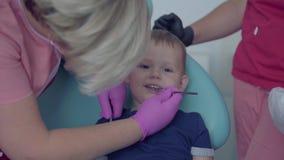 Dentysta sprawdza tooths mały beztroski chłopiec obsiadanie w krześle w medycznej masce i rękawiczki Niegrzeczny pacjent zbiory wideo