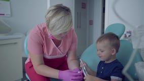 Dentysta w medycznej masce i rękawiczki gotowe sprawdzać tooths mały beztroski chłopiec obsiadanie w krześle femaleness zbiory wideo