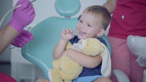 Dentysta w medycznej masce i rękawiczki gotowe sprawdzać tooths mały beztroski chłopiec obsiadanie w krześle Niegrzeczny zbiory wideo
