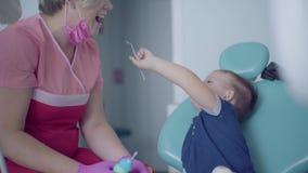 Dentysta w medycznej masce i rękawiczki gotowe sprawdzać tooths mały beztroski chłopiec obsiadanie w krześle Niegrzeczny zbiory