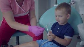 Dentysta w medycznej masce i rękawiczki gotowe sprawdzać tooths mały beztroski chłopiec obsiadanie w krześle w stomatologicznym zbiory
