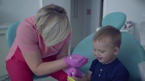 Dentysta w medycznej masce i rękawiczki gotowe sprawdzać tooths mały beztroski chłopiec obsiadanie z lustrem w krześle zdjęcie wideo