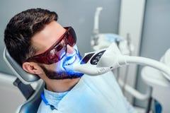 Dentysta zaczyna zęby bieleć procedurę z młodym człowiekiem zdjęcia stock