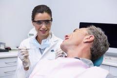 Dentysty mienia narzędzie podczas gdy patrzejący mężczyzna w klinice Obraz Stock