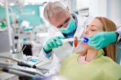 Dentysty use stomatologiczny instrument z światłem w stomatologicznej pracie Zdjęcia Royalty Free