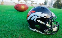 Denver broncos helmet and ball. ZAGREB , CROATIA - OCTOBER 28, 2015 :  NFL Denver Broncos replica helmet with NFL official bal on the fieldl, product shot Royalty Free Stock Image