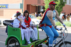 Denver, Colorado, de V.S. - 1 Juli, 2017: Duffman die twee geisha's in een pedicab drijven in Denver Comic Con Stock Afbeelding