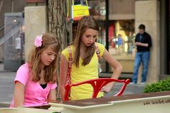 Two girls playing piano on 16th street in downtown Denver stock image