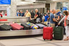 Baggage claim. Denver, Colorado, USA-June 22, 2016.  Travelers waiting for their luggage at the baggage carousel Royalty Free Stock Photo