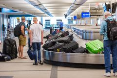 Baggage claim. Denver, Colorado, USA-June 22, 2016.  Travelers waiting for their luggage at the baggage carousel Royalty Free Stock Images