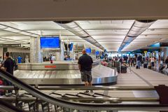 Baggage claim. Denver, Colorado, USA-June 22, 2016.  Travelers waiting for their luggage at the baggage carousel Stock Image