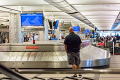 Baggage claim. Denver, Colorado, USA-June 22, 2016.  Travelers waiting for their luggage at the baggage carousel Royalty Free Stock Photos