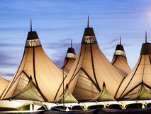Denver International Airport. Glowing tents of DIA at sunrise. Denver International Airport well known for peaked roof. Design of roof is reflecting snow-capped Stock Photos