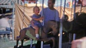 DENVER, LE COLORADO 1952 : Papa tenant la fille sur le tour d'amusement de carrousel de cheval clips vidéos