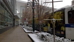 Denver Light Rail, Downtown Winter. Denver RTD Light Rail train passes the Colorado Convention Center as snow falls original sound and warning bells included stock footage