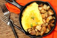 Denver Omelette- und Ranch-Kartoffeln in der Roheisen-Bratpfanne auf Tabelle Lizenzfreie Stockbilder
