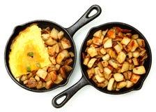 Denver Omelette- und Ranch-Kartoffeln in der Roheisen-Bratpfanne lokalisiert Lizenzfreies Stockbild