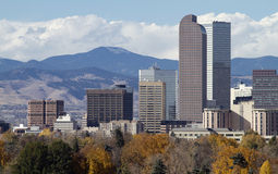 Denver Skyscrapers with Rocky Mountains. Distinctive Denver, Colorado skyscrapers, with the Rocky Mountains in the background and autumn trees in the foreground Stock Photos