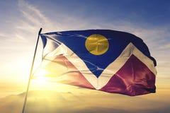 Denver-Stadthauptstadt von Colorado des Flaggentextilstoffgewebes Vereinigter Staaten, das auf den Spitzensonnenaufgangnebelnebel stockbild
