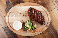 Denver steak with salad. And sauce. Wooden background Royalty Free Stock Images