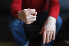 Deny or refuse to do something. Man shows a fig from the fingers, sitting in a chair royalty free stock images