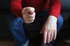 Deny or refuse to do something. Man shows a fig from the fingers, sitting in a chair stock image