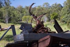 Depósito de chatarra con los registros y la maquinaria agrícola vieja Fotos de archivo libres de regalías