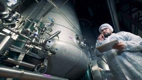 Depósito de destilación masivo y un especialista de sexo masculino observando su proceso de trabajo almacen de metraje de vídeo
