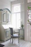 Departamento, cadeira e tabela da escrita pela janela fotografia de stock