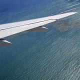 Departing. Square shot of airplane wings over shallow water Stock Image