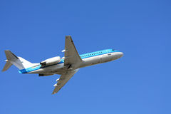 Departing airplane in a clear blue sky Royalty Free Stock Photography