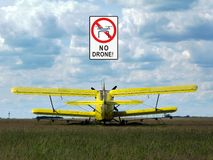 Departing airplane on grassy field and no drone label royalty free stock photo
