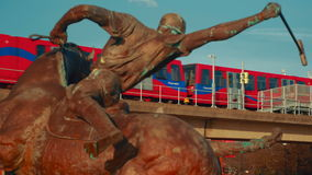 Departing DLR Train Framed by a Polo Player Statue stock video