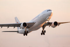 Departing MASkargo Airbus A330-223F aircraft in the sunset rays Stock Photos