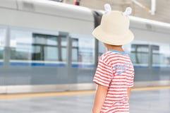 Boy watching train departing Stock Photo