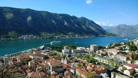 Departing from the pier, cruise ship and views of Kotorska red roofs. Boko-Kotor Bay Royalty Free Stock Photo