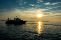 Departure of a Ferry Ship at Sunset Stock Images
