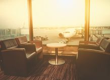 Departure lounge at the airport with seating and table with aircraft preparing for flight. In the background Stock Photos