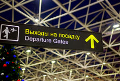 Departure sign in airport with christmas tree at background. Travel and lifestyle concept. Holidays and vacation. No people. Russian and English languages Stock Photo
