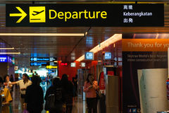 Departure Sign at Singapore Changi Airport. A departure sign hangs over busy travellers at Changi Airport Terminal 1 departure hall. Opened in 1981, Changi Stock Images