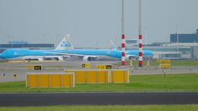 Departure traffic in Shiphol airport. Amsterdam, The Netherlands - July 24, 2017: KLM Royal Dutch Airlines Boeing 747 PH-BFC and Boeing 777 taxiing before take stock footage