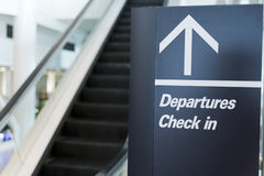 Departures Check in sign. At an airport with an arrow. Black sign with white writing. Sign positioned next to an escalator and out of focus escalator can be Stock Images