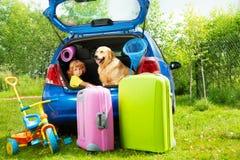 Depature aspettante del bambino, del cane e dei bagagli immagine stock libera da diritti