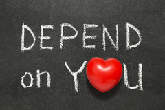Depend on you. Phrase phrase handwritten on blackboard with heart symbol instead of O Stock Photo