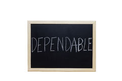 DEPENDABLE written with white chalk on blackboard Royalty Free Stock Photography