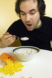 Dependency. A man feeding himself medication with a spoon. Metaphor for addiction, dependency, etc Stock Photography