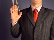 Dependency businessman. Marionette businessman makes a welcome gesture, hand on the ropes Royalty Free Stock Image