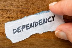 Dependency concept and theme written on old paper on a grunge background. The word Dependency concept and theme written on old paper on a grunge background stock image