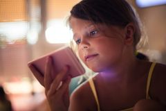 Dependency. Little girl lying on bed and using smart. Copy space. Close up royalty free stock photos